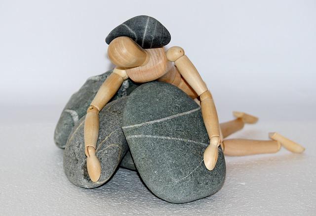 Datei:Holzfigur unter Steinen Depression.jpg
